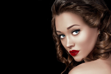 Beauty Fashion Woman Model Face Closeup. Beautiful Professional Make up and Hairstyle. Red Lips and Long Eyelashes. Gorgeous Glamour Lady Portrait. Isolated on Black Background...