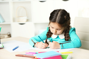 Cute little girl doing her homework, close-up, on home interior background