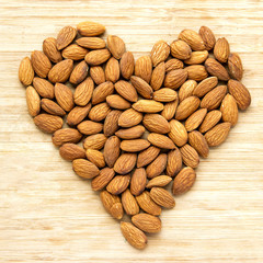 Heart of Almond Nuts over Wooden Background. Healthy Food Concept.