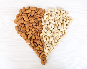 Heart of Almond Nuts and Cashew Nuts over White Wooden Background. Healthy Food Concept.