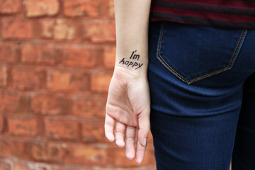 Hand of young woman with tattooed phrase on it, on wall background, close-up