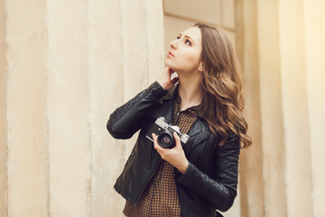 Portrait of a pretty young tourist taking photographs with vintage retro camera