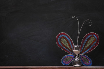 Concept of butterfly with hourglass and chalk on black background