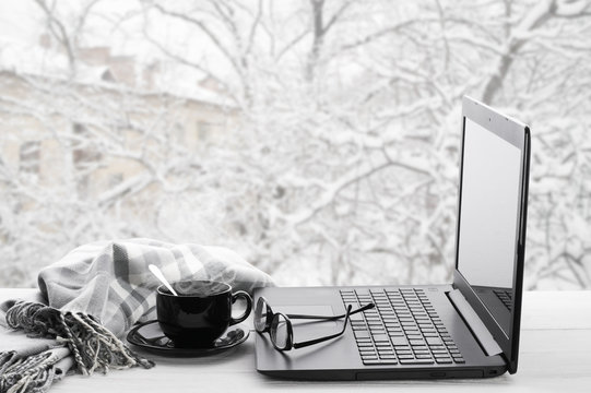 Laptop and coffee on winter window