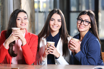 Attractive stylish girls  hold cup of coffee sitting in cafe