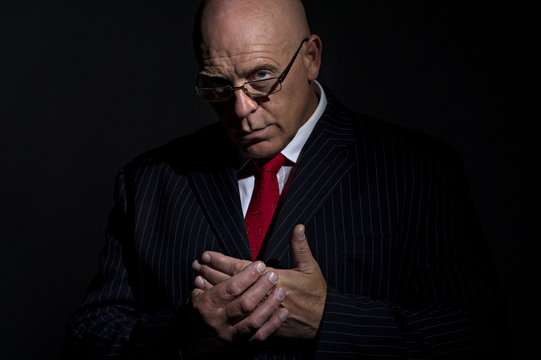Portrait of mature male rubbing his hands together. He is looking into camera over the rim of his glasses