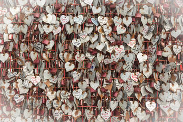 love - a metallic fence with hearts and padlocks with couples names