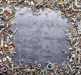 Assorted screw nuts and bolts frame on metal texture background