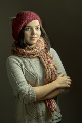 Close up portrait of a smiling young woman wearing beret hat and scarf posing with arms crossed on dark grey background