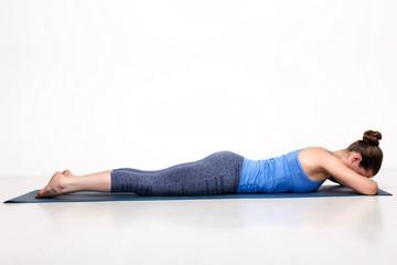 Sporty woman relaxes in yoga asana Makarasana