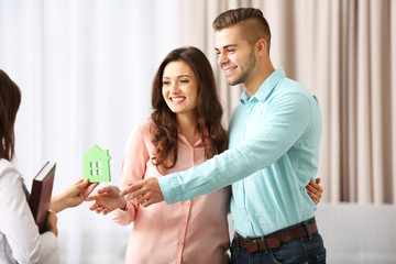 Estate agent giving model of house to  couple, on light background