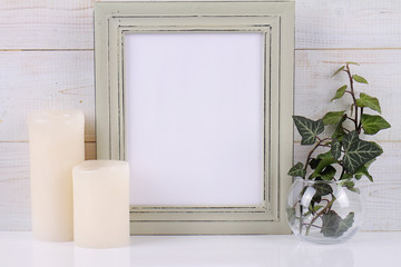 Empty picture frame with copy space blank on white rustic background and Ivy plant.  Scandinavian style home interior decoration