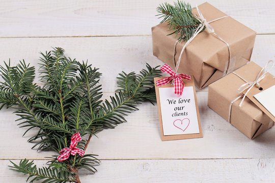 Business Marketing Ideas for Christmas Client Gifts. Vintage gift boxes  for customers with  We love our clients  tag on white background. New year presents and fir branch on white rustic table