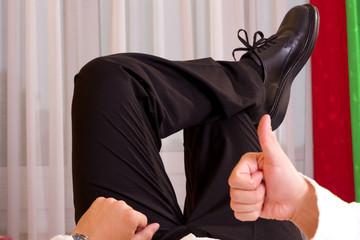 zufrieden zeigt der Geschäftsmannden Daumen nach oben im Hotel Zimmer