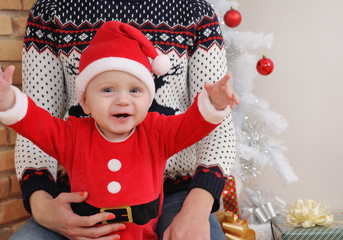 happy cute little baby boy in Santa suit sitting on mother's kne