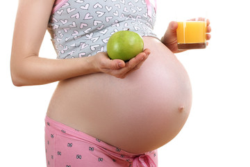 a pregnant woman in pyjamas holding a green Apple isolated on white background
