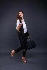 Pretty female business lady in a black jacket white shirt, umbrella, handbag on a dark background. Studio shot. Walk