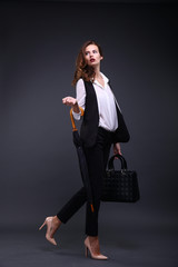 Business lady in a black jacket white shirt, umbrella, handbag on a dark background. Studio shot