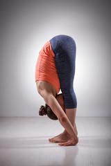 Sporty fit woman practices yoga asana Uttanasana