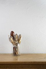 Jar with vintage silverware on wooden table