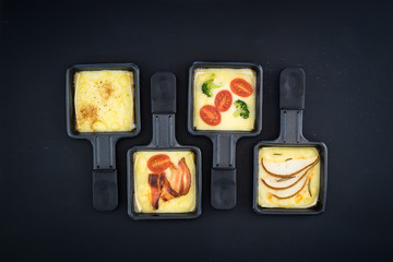Four small square raclette pans with melted cheese and different ingredients: paprika, bacon, cherry tomatoes, broccoli and pear slices
