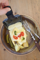 Pouring melted raclette cheese from square raclette pan onto boiled potatoes and pickles
