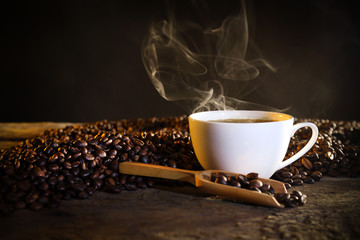 Cup of coffee and coffee beans on table