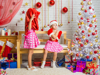 Girl wearing Santa Claus bag on his head, the other girl was offended sitting on the bench