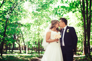 Happy couple bride and groom embracing they stand in a forest