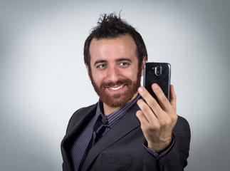 Smiling businessman is using his smartphone to take a selfie