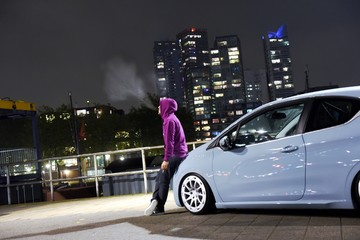 Hooded boy smokes a cigarette sitting on the hood of his car and watch the panorama of the city after the sunset. Rotterdam skyline at the night.