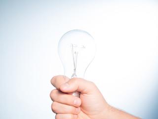 Hand holding an incandescent light bulb
