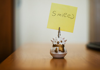 Single blank note paper with single word. Figurine toy on office desk. Lifestyle