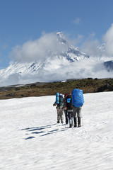 Group of tourists climbing the snowfield on background volcanoes