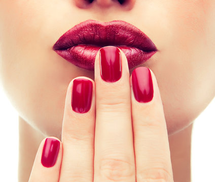 Beautiful model  shows red  manicure on nails. Red lips .Luxury fashion style, manicure nail , cosmetics and makeup .