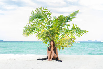 Tropical vacation. Young beautiful woman and palm on the beach.