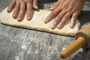 Hands making dough on stone table