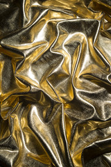 Gold background shining in an abstract of folds and shadowed creases