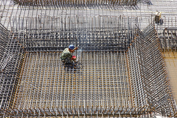 worker in the construction site making reinforcement metal frame