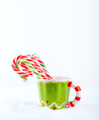Christmas candy cane in the cup on the snow