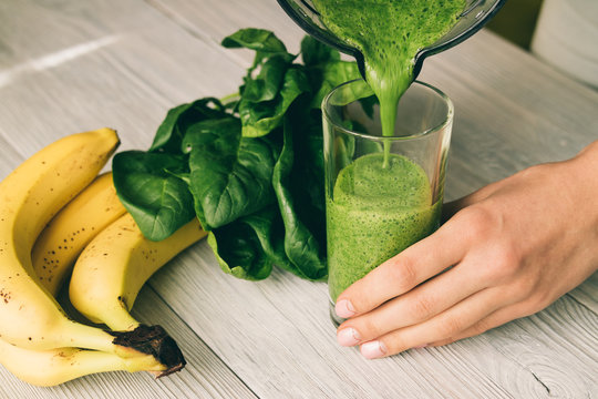 Female hand pours a smoothie of banana and spinach in glass on a