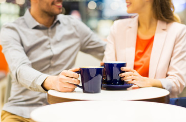 close up of happy couple drinking coffee in mall