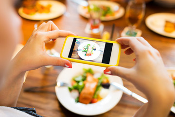 hands photographing food by smartphone