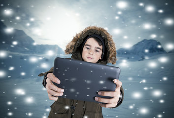 child warm with the tablet in the snow