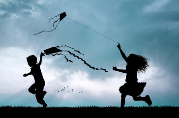 children with kite silhouette at sunset