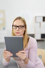 junge frau liest informationen am tablet-pc