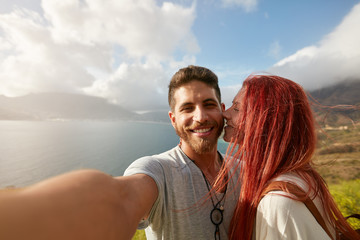 Romantic young couple taking a selfie outdoors