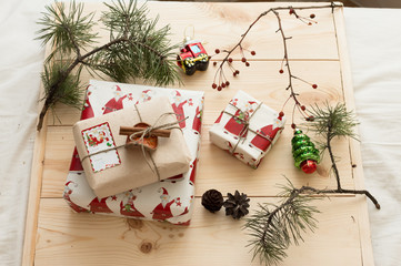 New Year gift packaging hand made with cinnamon stick on a background of pine cones, pine branches and Christmas decorations on a natural wooden background