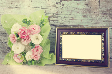 rose in vase and frame of wooden background
