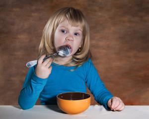 Завтрак маленького ребенка. Девочка блондинка ест кашу ложкой. Теплого, коричневого оттенка фон